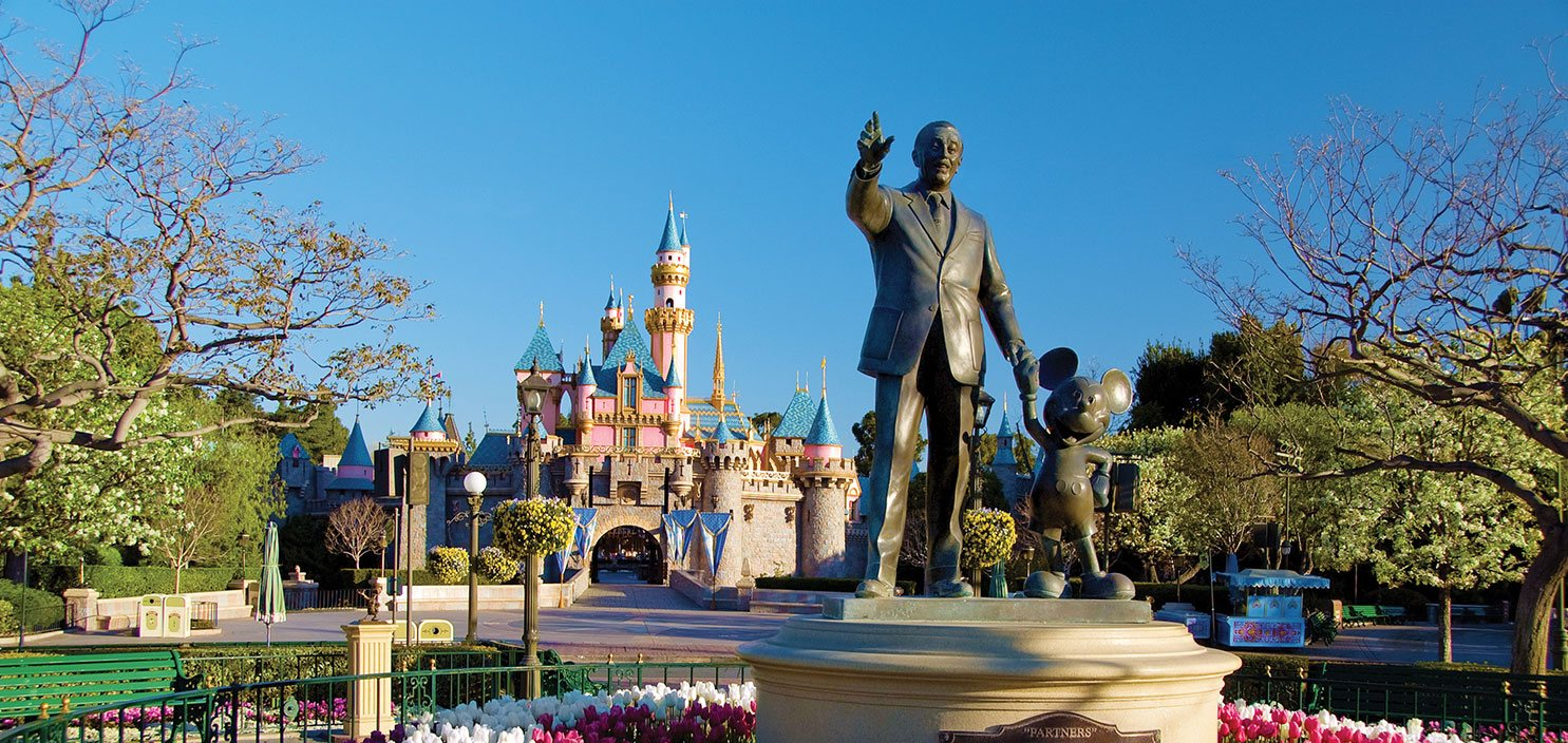Statue of Walt Disney and Mickey Mouse in front of Castle