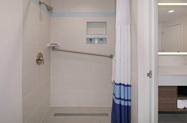 A walk in shower with grab bars at the Tropicana Inn and Suites Hotel near Disneyland in California