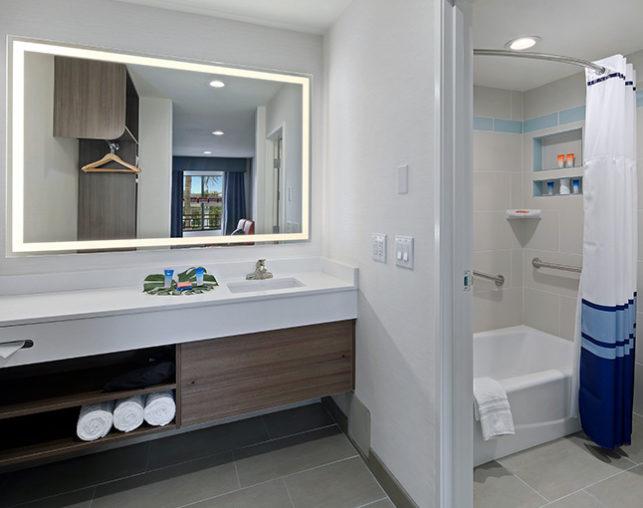 A spacious bathroom featuring a well-lit mirror, custom bath amenities & shower at our hotel near Disneyland