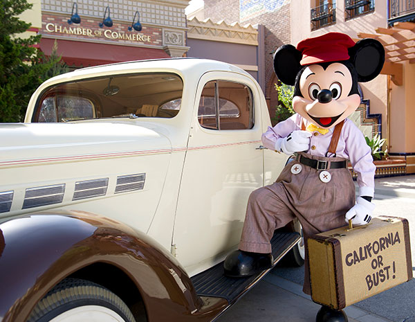 Mickey Mouse next to old car caring suitcase saying