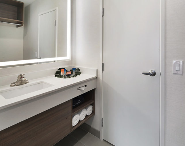 The bathroom vanity includes custom bath amenities, a spacious counter, hair dryer & more
