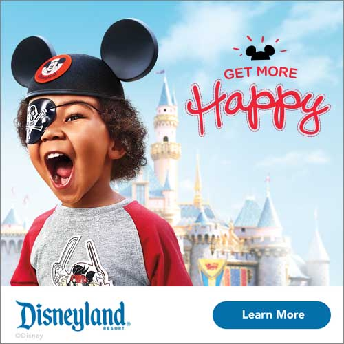 Young boy with mickey mouse ears and an eye patch standing in front of the Disneyland castle.