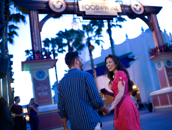 couple holding hands and wine at Disney Food & Wine Festival