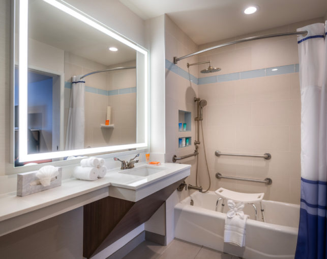 ADA double queen hotel room with shower/tub combo and shower chair near Disneyland@