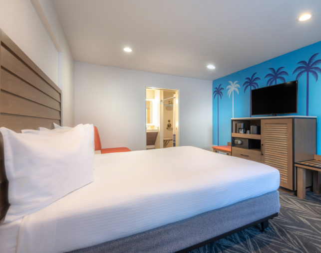 Side view of the ADA king guest room bed, tv, and bathroom entrance at Camelot Inn & Suites