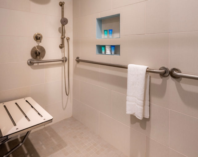 ADA king roll in shower with removable shower head, bars and bench at our Disneyland® hotel