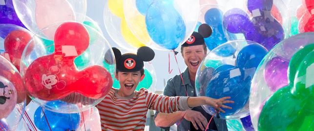 kids running through disneyland balloons